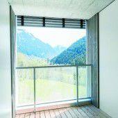 Loggia mit Stirnfransen: Die herabgezogenen Latten der Fassade wirken wie ein Rahmen für die Landschaft.