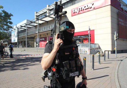 Einer der Polizisten postiert sich vor dem Kinokomplex, in dem sich ein Mann mit Geiseln verschanzt hat.