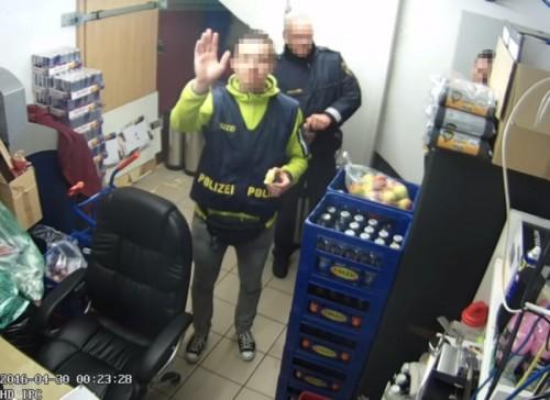 Nichts dabei gedacht? Einer der Beamten winkt fröhlich in die Linse der Überwachungskamera.