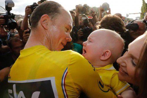 Tour-Sieger Christopher Froome trägt seinen Sohn Kellan im Arm, rechts seine Frau Michelle Cound.