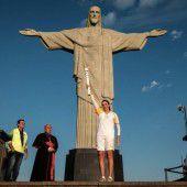 Die olympische Flamme unter der Christus-Statue