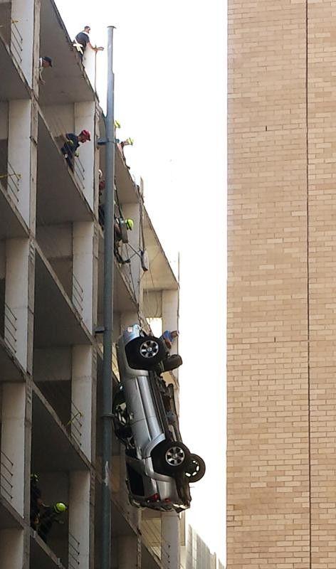 Die Einsatzkräfte seilten den Wagen in die Häuserschlucht zwischen Parkhaus und gegenüberliegendem Gebäude ab. Foto: Reuters
