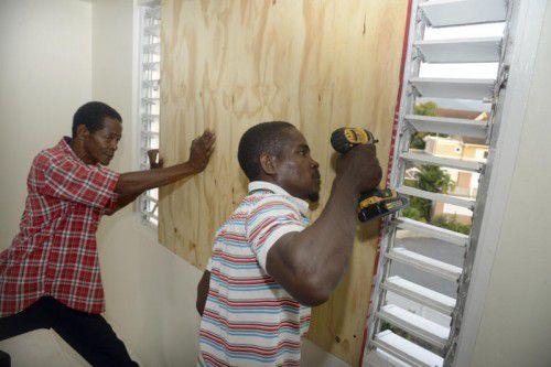 Bewohner verbarrikadieren vorsorglich die Fenster.  Foto: ap