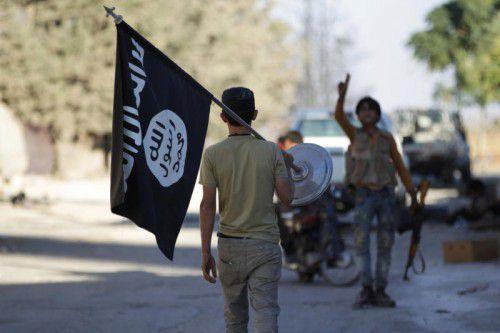 Ein Rebell entfernt die Flagge der Terrormiliz. Foto: reuters