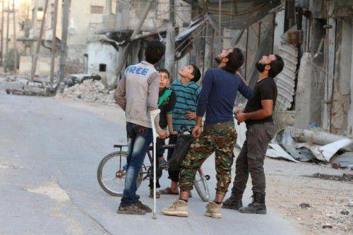 In Furcht vor dem nächsten Luftschlag beobachten Männer aus Aleppo den Himmel. Die nordsyrische Stadt versinkt in der Gewalt. Foto: AFP