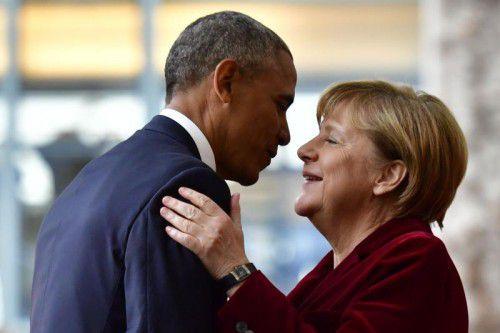 Obama und Merkel begrüßten sich mit einem Kuss auf die Wange. Foto: AFP