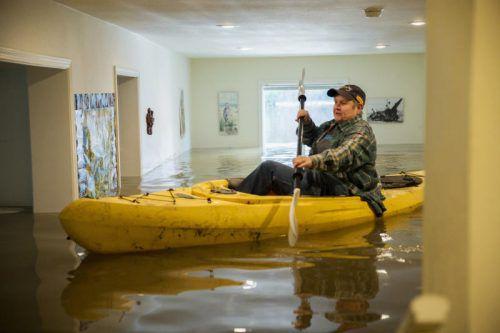 Mit dem Kajak durchs Wohnzimmer: Auch das Haus von Lorin Doelemann in Guerneville steht unter Wasser. Foto: AP
