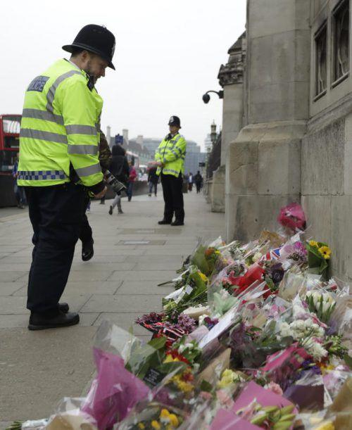 Ein Polizist besucht die Gedenkstätte beim Parlament. Foto: ap