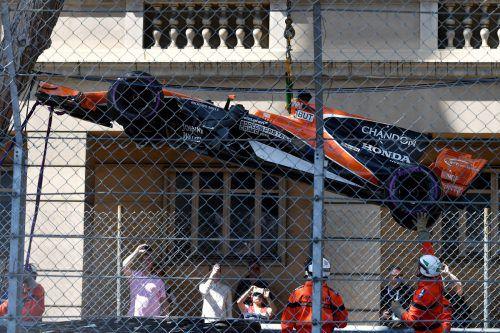 Der McLaren von Jenson Button wird von der Strecke gehoben. Foto: afp