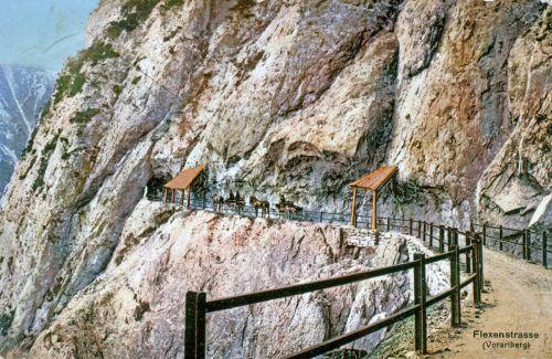 Flexenstraße zwischen Hölltobel und dem Weißen Tunnel um 1910. Das erste Schutzgeländer bestand aus Eisenschienen. Zwischen den hölzernen Galerien stehen zwei Pferdefuhrwerke.