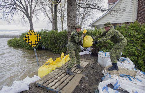 Mitglieder der kanadischen Armee bauen eine Barriere aus Sandsäcken aufgrund der steigenden Überschwemmungen in Montreal. Foto: AP