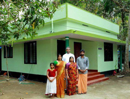 Pfarrer Georg Taniyath mit einer Familie vor deren neuem Haus.