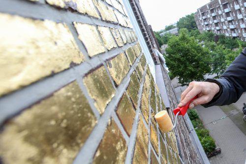 Eine 300 Quadratmeter große Hauswand wird mit Blattgold bepinselt. Das Kunstprojekt hatte bereits im Vorfeld für viel Wirbel gesorgt. APA