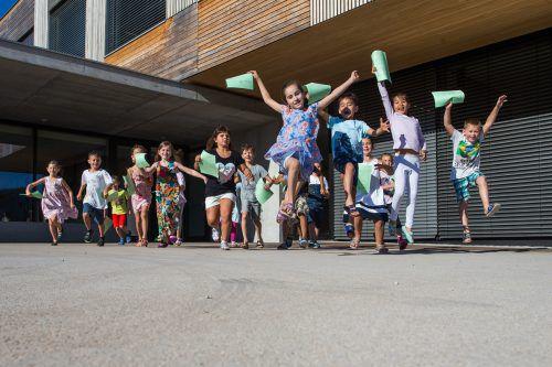 Die 18 Schüler der Klasse 1b stürmen mit ihren Zeugnissen in der Hand auf den Schulhof. Die Sommerferien können beginnen. Foto: VN/Steurer