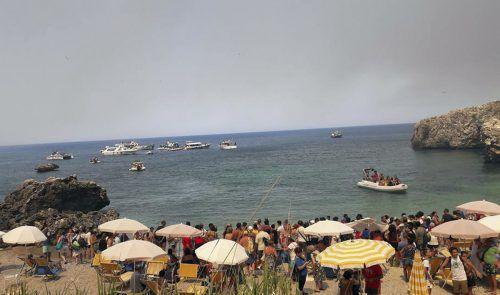Diese Touristen des Dorfs San Vito Lo Capo auf Sizilien wurden mit Booten vor dem Feuer in Sicherheit gebracht.  Foto: AP