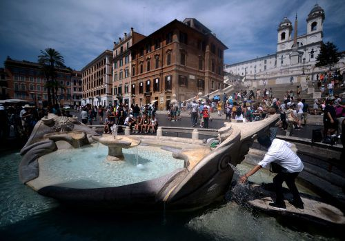 Eine Person füllt eine Flasche mit Wasser aus dem Barcaccia-Brunnen auf Roms Piazza di Spagna. Foto: AFP