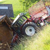 Traktor rollt gegen eine Hauswand
