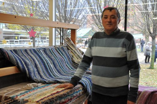 Voller Stolz zeigt Viktor seine selbst gefertigten Arbeiten auf dem Webstuhl. cm