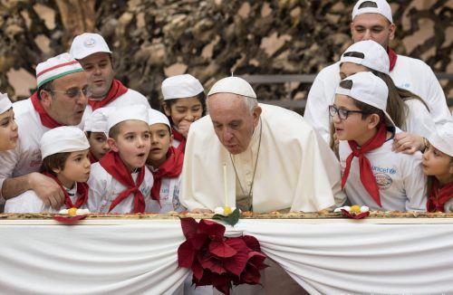 Zusammen mit Kindern bläst der Papst eine Geburtstagskerze aus. AP