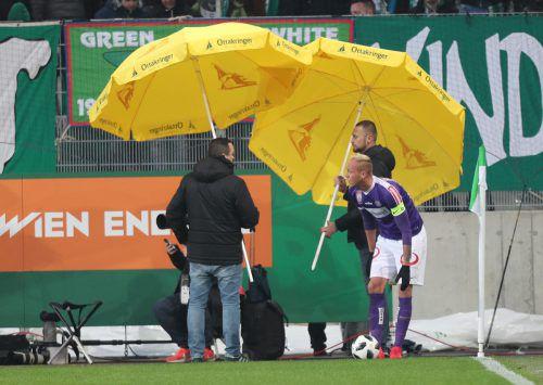 Austria-Wien-Kapitän Raphael Holzhauser musste beim Eckball mit Schirmen geschützt werden. Dennoch traf ihn ein Feuerzeug aus dem Rapid-Fansektor.gepa