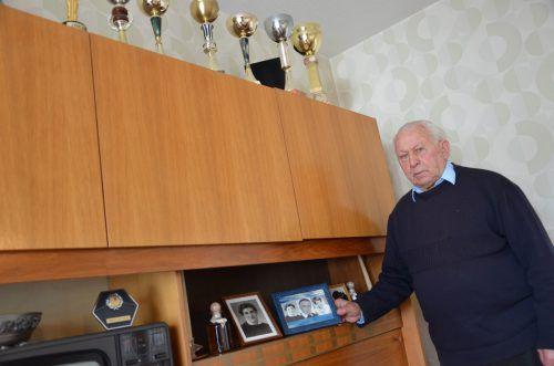 Sepp Reiner zeigt ein Foto, auf dem er mit Frau und Tochter zu sehen ist. Die Pokale auf dem Wohnzimmerschrank hat er bei Radrennen gewonnen. Hrj