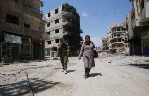 Begleitet von einem Regierungssoldaten kehrt eine Bewohnerin der zerstörten Stadt Zamaika in Ost-Goutha heim. afp