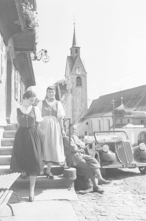 Dieses Bild zeigt eine Autofahrt in den Bregenzerwald im Jahr 1939. Im Hintergrund ist der Kirchturm von Schwarzenberg zu sehen.Sammlung Risch-Lau, Vorarlberger Landesbibliothek