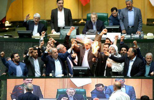Aus Protest gegen den Ausstieg der USA aus dem Atom-Deal verbrennen iranische Abgeordnete im Parlament in Teheran eine US-Fahne.AFP