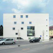 """<p class=""""factbox"""">Der Kreuzung zeigt das Bankgebäude die kalte Schulter, während die Südfassade durch ein riesiges und eine Reihe scheinbar frei angeordneter quadratischer sowie eine vertikale Reihe kleiner runder Fenster gegliedert ist.</p>"""