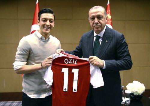 DFB-Teamspieler Mesut Özil überreicht Recep Erdogang (r.) ein Arsenal-Trikot. ap