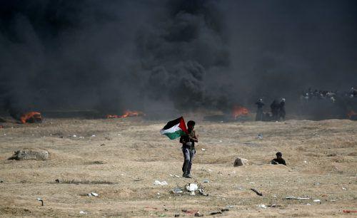 Ein Demonstrant schwenkt an der Grenze zum Gazastreifen eine palästinensische Flagge.AFP