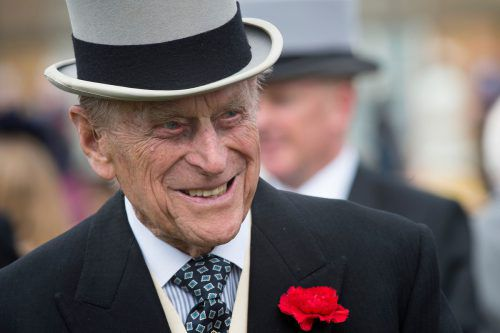 (FILES) In this file photo taken on May 16, 2017 Britain's Prince Philip, Duke of Edinburgh greets guests at a garden party at Buckingham Palace in London. Prince Philip has been at the queen's side since they wed in 1947, but may not be at the wedding after the family revealed he was still recovering from hip surgery. A naval officer, he served in World War II and witnessed the Japanese surrender. He retired from royal duties in 2017. The duke is renowned for his off-the-cuff remarks. / AFP PHOTO / POOL / Victoria Jones