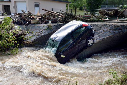 In Rheinland-Pfalz hängt ein demoliertes Kleinauto im Wasser an einer Brücke. apa