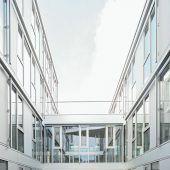 """<p class=""""factbox"""">Viel Licht bringt ein Innenhof in den noch rohen Baukörper des Geschäftsgebäudes. Das ebenso wie das Bankhaus aus Stahlbeton gebaut und weiß verputzt ist.</p>"""