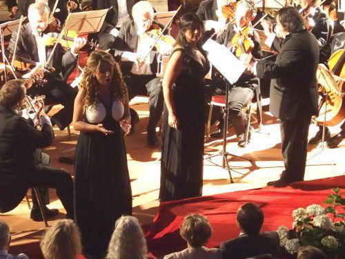 Die Solistinnen Tamta Tarielle und Alexandra Zabala mit dem Arpeggione-Orchester und dem Dirigenten Muhai Tang im Palasthof von Hohenems. JU