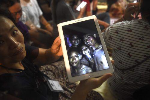 Happy End in Thailand: Familienmitglieder sehen die Bilder der entdeckten, noch in der Höhle befindlichen Buben und ihres Trainers. AFP