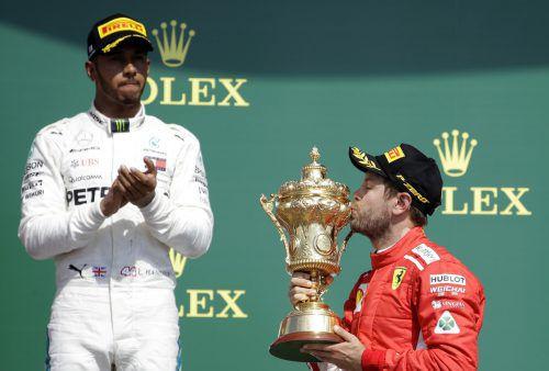Sebastian Vettel herzt den Siegerpokal von Silverstone, Lewis Hamilton schaut nach Platz zwei im Heimrennen angesäuert.ap