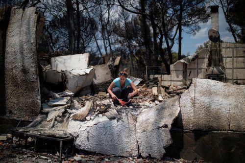 Überlebende der Brandkatastrophe suchen in den Brandruinen nach ihren Habseligkeiten. Hunderte Häuser sind einsturzgefährdet und unbewohnbar. AFP