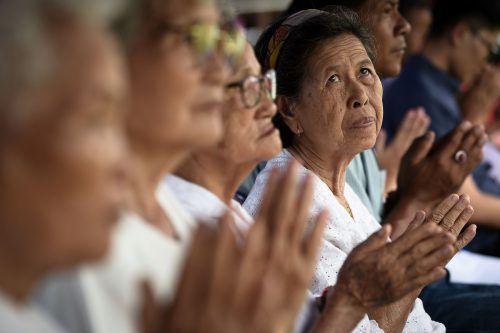 Vor dem Höhleneingang haben sich Angehörige zum Gebet versammelt. AFP