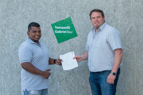 Vorarlbergers erster angehender Bautechnischer Assistent, Suprean Leitner, erhält seinen Lehrvertrag von Markus Fritsch, Ausbildner bei Tomaselli Gabriel Bau. TGB