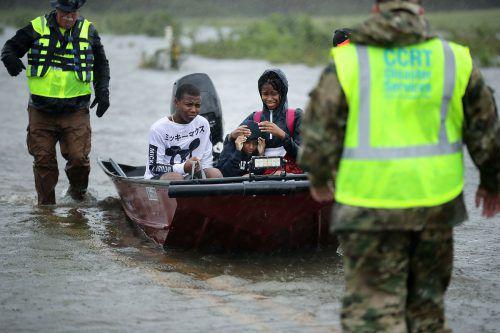 Dutzende Menschen mussten aus über-fluteten Häusern gerettet werden. AFP