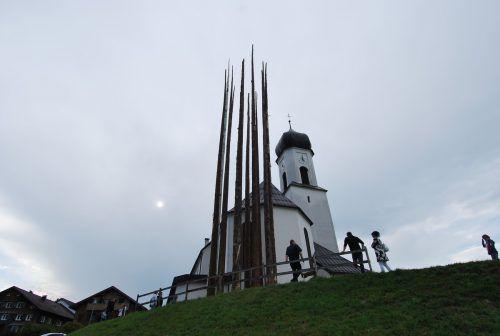Der Turm Paula des Dornbirner Künstlers Angelo Roventa ragt neben der Kirche in Andelsbuch in die Höhe. ERH