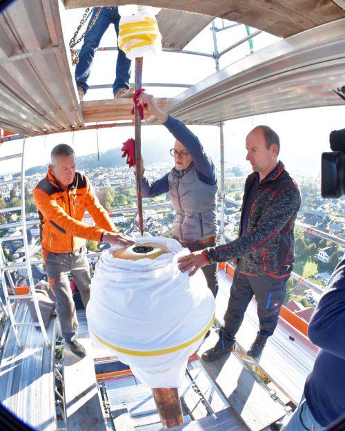Die Turmzier wird wieder in die Spitze des Höchster Kirchturms gesenkt. Auf dem Bild Manfred Brunner, Gerüstbau, Restauratorin Nicole Mayer und Spengler Ronny Stibane. AJK