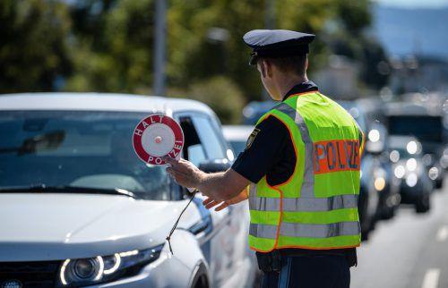 Ein bayerischer Polizist kontrolliert ein Auto an der Grenze. DPA