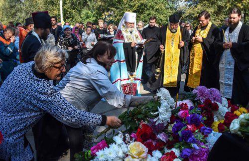 Menschen legten vor der Schule Blumen für die Opfer nieder. AFP