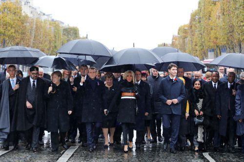 Symbolträchtiger Akt bei Gedenkfeier zum Ende des Ersten Weltkriegs in Paris: Trotz des Regens legten die Ehrengäste die letzten Meter zum Triumphbogen zu Fuß zurück. ap