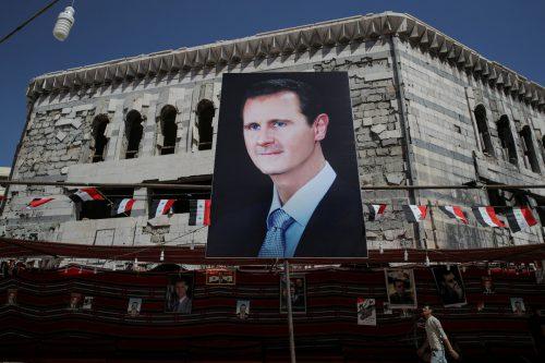 Ein Banner zeigt den Machthaber in Damaskus. Der kurdische Hilferuf bietet ihm Gelegenheit, aus dem Krieg ohne territoriale Einbußen hervorzugehen. reuters
