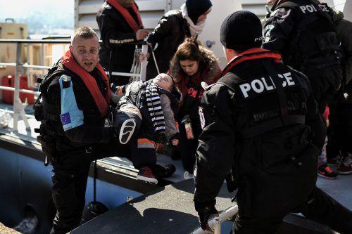 Ein Frontex-Beamter (l.) hilft Bootsflüchtlingen, die auf der griechischen Insel Lesbos ankommen. afp