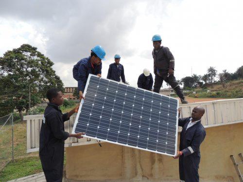 Eine Photovoltaikanlage zur Stromerzeugung wird auf das Dach gehoben.
