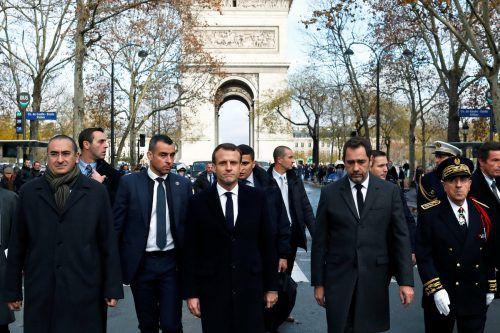 Emmanuel Macron (M.) schaut sich das Resultat der Krawalle vor Ort an.reuters